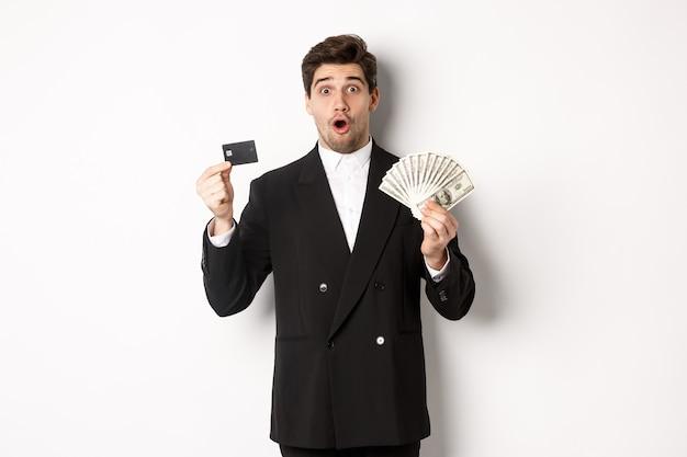 Ritratto di un bell'uomo sorpreso che mi adatto, mostrando la carta di credito con soldi, in piedi su sfondo bianco