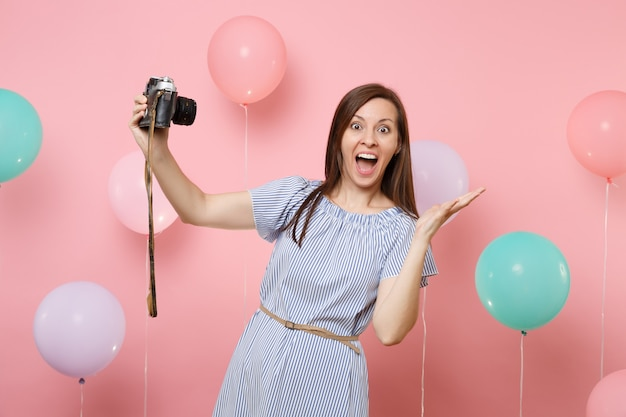 Portrait of surprised happy woman in blue dress doing selfie on retro vintage photo camera spreading hands on pink background with colorful air balloons. birthday holiday party people sincere emotion.