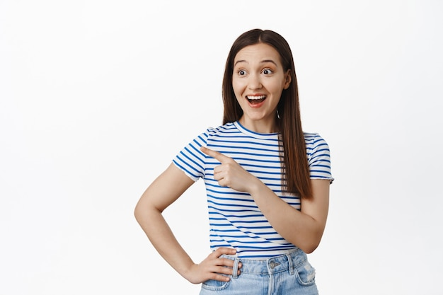 Portrait of surprised, happy young brunette woman checking out sale, pointing finger and looking left at banner, smiling amused, standing against white wall
