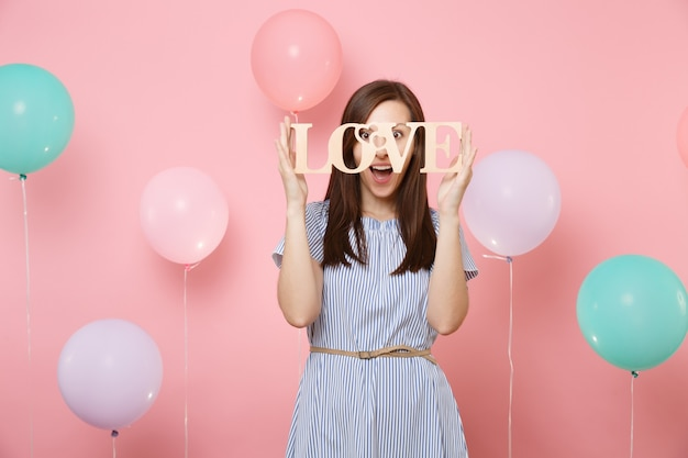 Portrait of surprised happy young woman in blue dress holding wooden word letters love on pastel pink background with colorful air balloons. birthday holiday party, people sincere emotions concept.