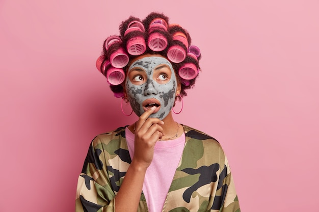 Il ritratto della casalinga sorpresa applica la maschera di argilla sul viso si chiede sopra fa l'acconciatura con i bigodini indossa le pose dell'abito domestico contro il muro rosa. procedure di bellezza a casa.