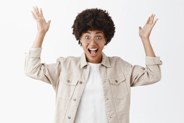 Ritratto di donna afroamericana eccitata sorpresa e impressionata in occhiali e camicia beige che alza le palme in alto nel gesto di stupore che sorride ampiamente dalla gioia e dalla felicità