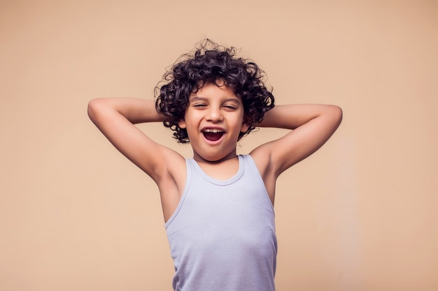 Portrait of surprised kid boy with curly hair. children and emotions concept