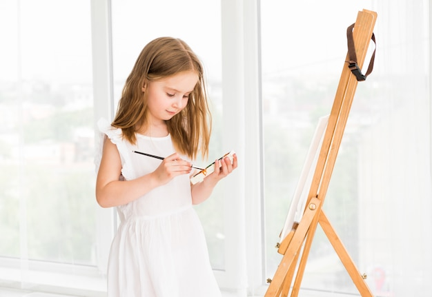 Portrait of surprised little girl painting a picture