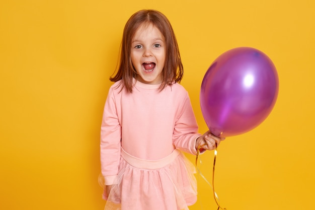 Portrait of surprised little girl with dark straight hair standing over yellow studio beautiful clothes, holding purple ballon in hands