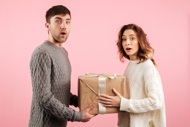 Portrait of surprised loving couple dressed in sweaters