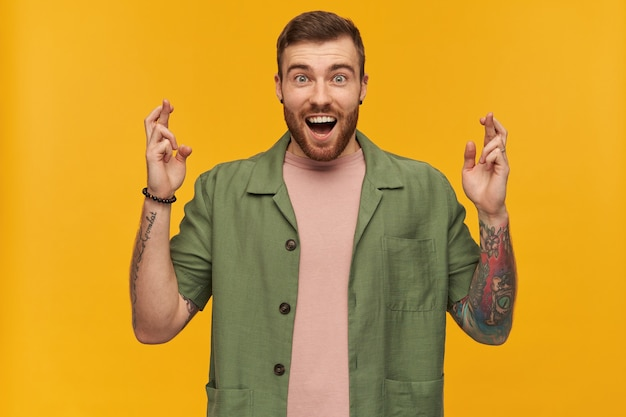 Portrait of surprised male with brunette hair and beard. wearing green short sleeves jacket. has tattoos. keeps fingers crossed, making a wish.  isolated over yellow wall