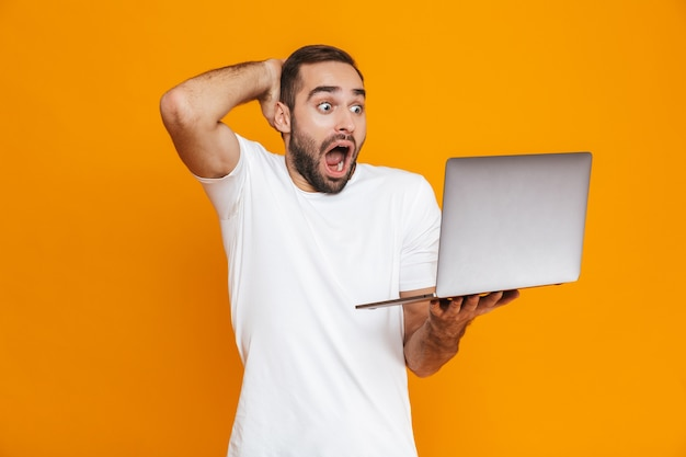 Portrait of surprised man 30s in white t-shirt holding silver laptop, isolated