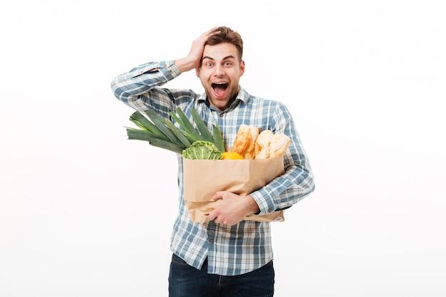 Portrait of a surprised man holding paper bag