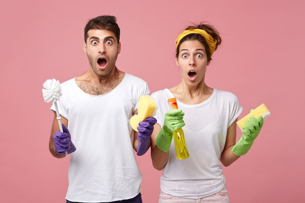 Portrait of surprised man wearing protective gloves holding brush and woman with sponge and detergent looking with widely opened eyes and mouths