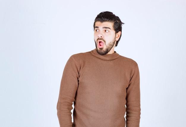 Ritratto di uomo sorpreso con la bocca aperta e alza le sopracciglia con sorpresa e soggezione. foto di alta qualità