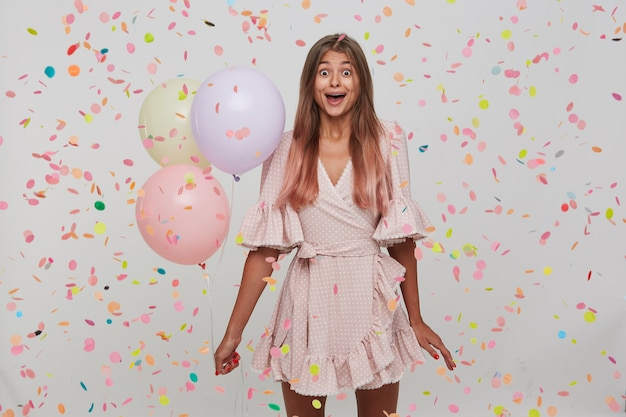 Portrait of surprised pretty young woman with long dyed pastel pink hair and opened mouth celebrating birthday, holding colorful baloons in hand