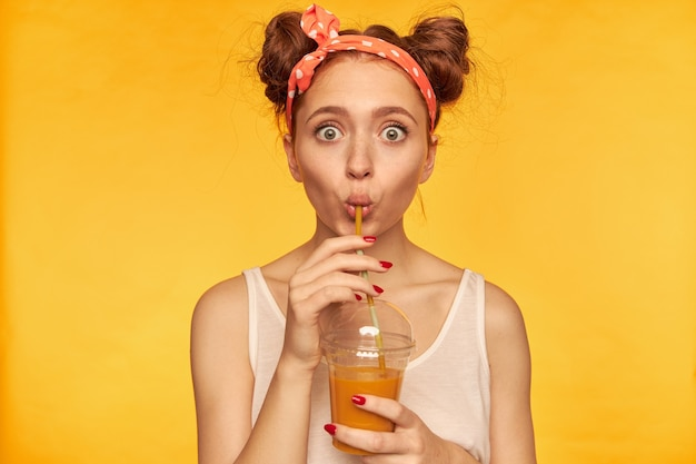 Portrait of surprised, red hair girl with red doted hairband. shocked with taste, make a sip. wearing white shirt and holding her smoothie