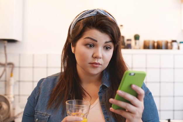 Portrait of surprised shocked young chubby female drinking homemade citrus detox juice, using smart phone, being astonished with unexpected news. people, healthy lifestyle and technology concept