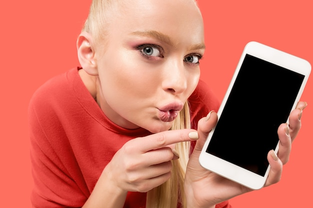 Portrait of a surprised, smiling, happy, astonished girl showing blank screen mobile phone isolated over coral background.