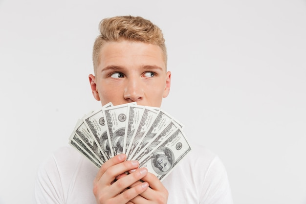 Portrait of a surprised teenage boy holding money banknotes