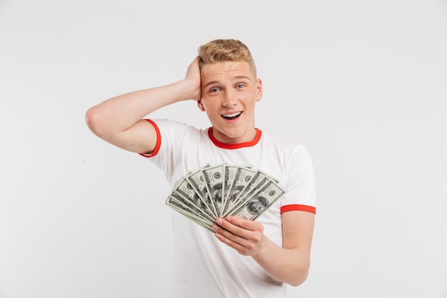 Portrait of a surprised teenage boy holding money