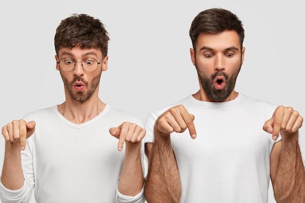 Ritratto di due commessi barbuti sorpresi puntano verso il basso con espressioni sbalordite, diciamo wow, bocche aperte aperte, stand spalla a spalla, isolato su un muro bianco. concetto monocromatico