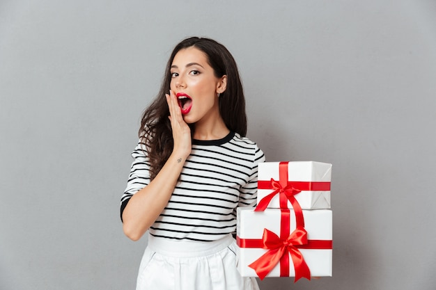 Portrait of a surprised woman holding stack of gift boxes