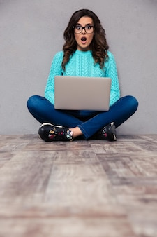 Portrait of surprised woman sitting on the floor with laptop and  on gray wall