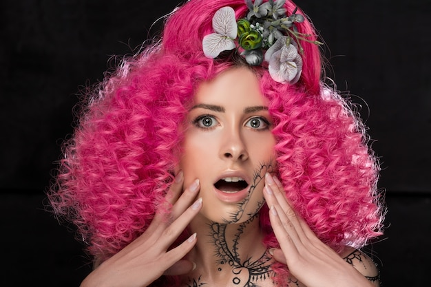 Portrait of surprised young attractive caucasian girl model with afro style curly bright pink hair