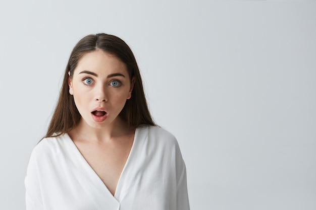 Portrait of surprised young beautiful businesswoman with opened mouth .