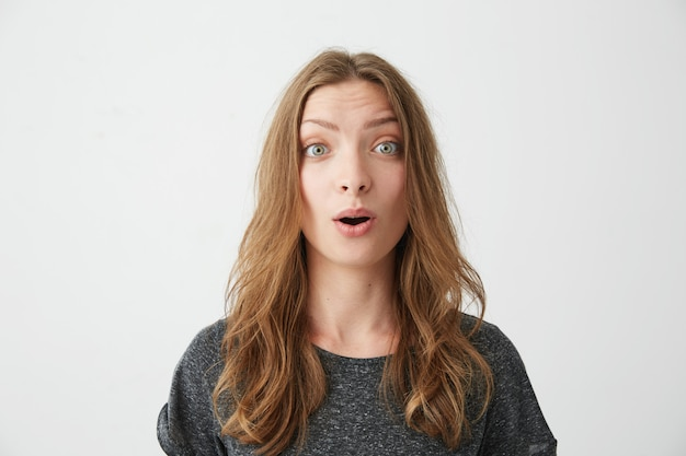 Portrait of surprised young beautiful girl with opened mouth .