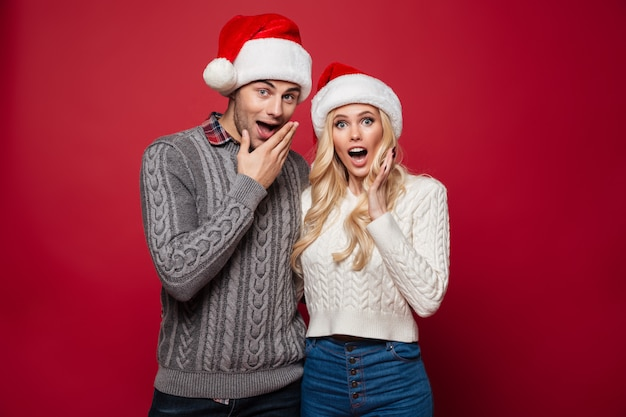 Portrait of a surprised young couple in christmas hats