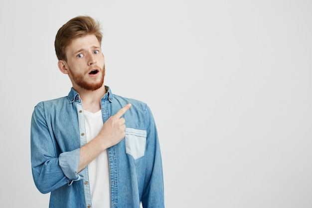 Portrait of surprised young handsome man with opened mouth pointing finger up.
