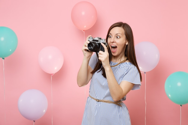 Portrait of surprised young happy woman in blue dress take pictures on retro vintage photo camera on pink background with colorful air balloons. birthday holiday party people sincere emotions concept.