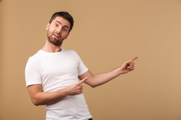 Portrait of a surprised young man casually dressed standing isolated over beige, pointing away at copy space