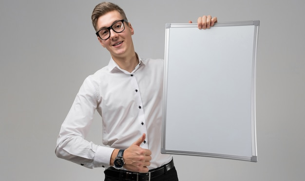 Portrait of surprised young man in glasses with clean board and shows sign super isolated  white