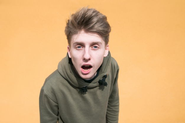 Portrait of a surprised young man on an orange wall.