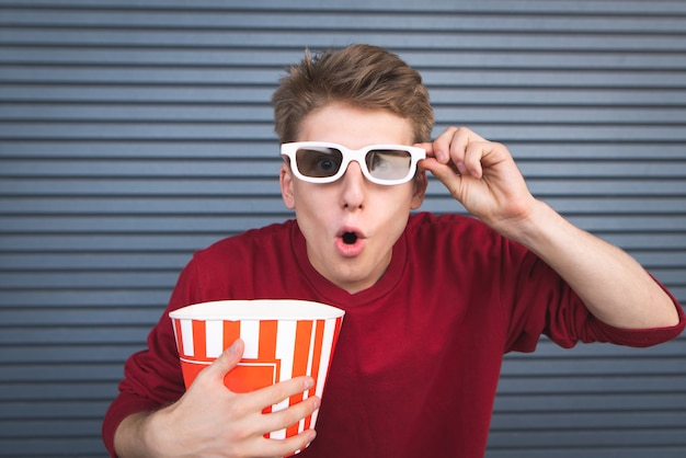 Portrait of a surprised young man watching a movie in 3d glasses with a cup of popcorn in his hands