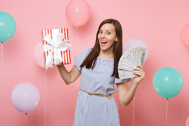 Portrait of surprised young woman in blue dress holding bundle lots of dollars cash money and red box with gift present on pink background with colorful air balloons. birthday holiday party concept.