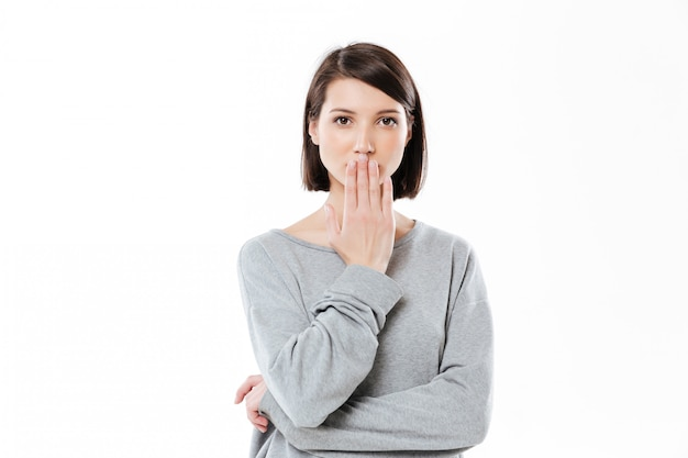 Portrait of a surprised young woman covering her mouth with hand isolated over white