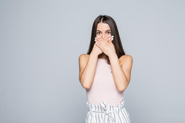 Ritratto di una giovane donna sorpresa che copre la bocca con le mani isolate sul muro bianco