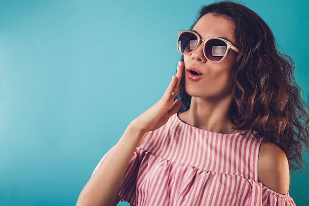Portrait of a surprised young woman wearing sunglasses on blue wall