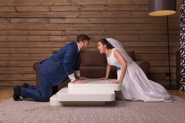 Portrait of swearing bride and groom, newlyweds relationship on wooden room