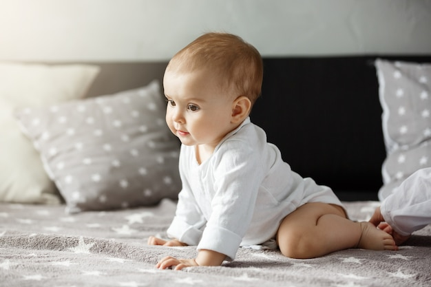 Portrait of sweet  baby sitting on cozy bed. child looking aside and happily crawls to mother. family, motherhood concept.