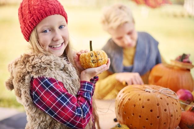 Portrait of sweet little girl with pumpkin
