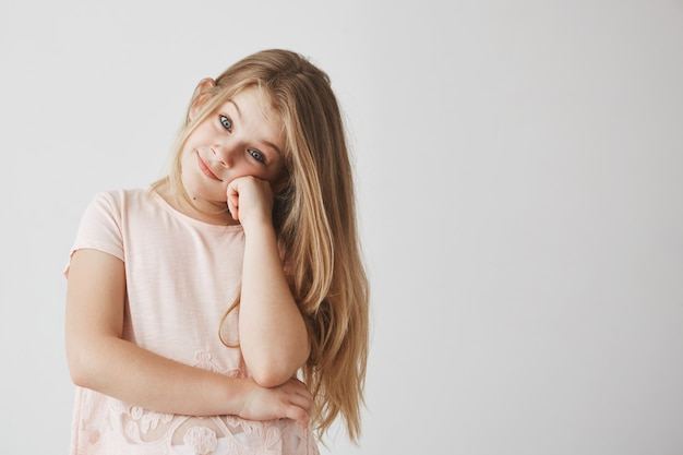 Portrait of sweet small girl with light long hair dressed in pink t-shirt  with joyful look, holding head with hand.