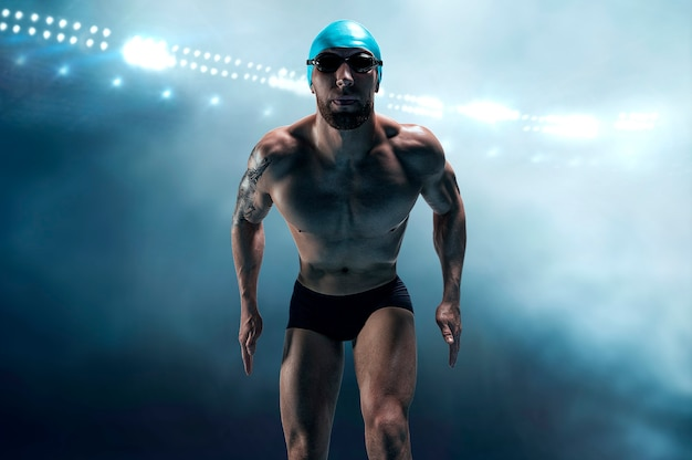 Portrait of a swimmer on the background of a sports arena. athlete is preparing for the jump