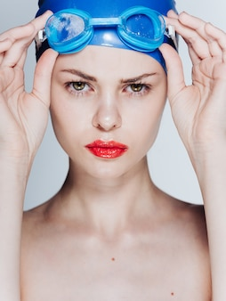 Portrait of a swimmer in a blue cap and glasses with bright makeup red oaks.