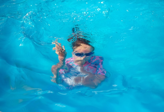 Portrait of a swimmer girl of 8 years old, in a bright swimming suit and blue glasses, located in an open-air pool with blue water, under water, during scuba diving