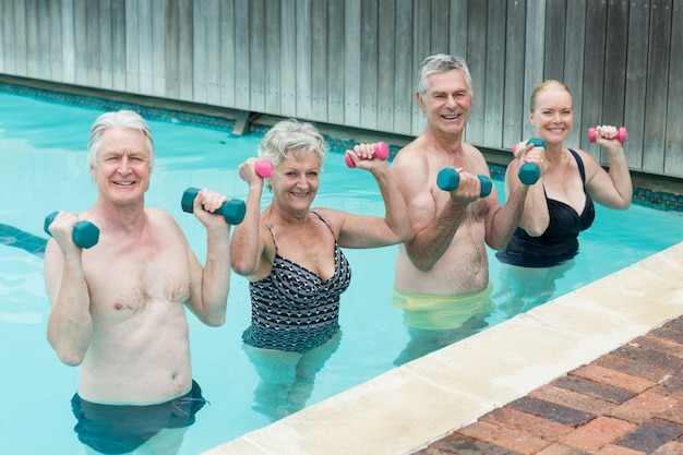 Portrait of swimmers weightlifting in swimming pool