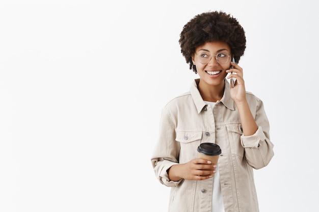 Ritratto di loquace amichevole e attraente modello femminile dalla carnagione scura in bicchieri e maglietta che tiene tazza di caffè di carta e parlando al cellulare guardando a sinistra