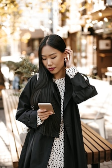 Portrait of tanned asian woman in black trench coat and white polka dot dress stands outside and chats at phone