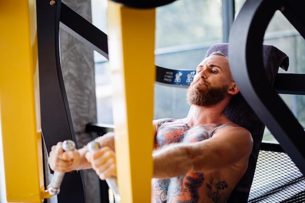Ritratto di uomo barbuto tatuato che lavora sulla macchina pressa torace in palestra vicino alla finestra