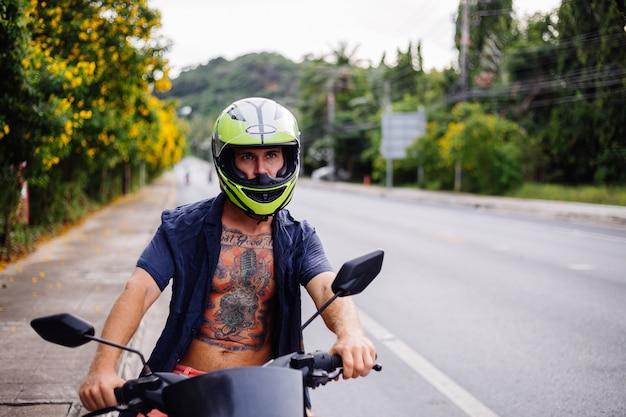 Ritratto del maschio tatuato del motociclista in casco giallo sulla moto sul lato della strada trafficata in thailandia